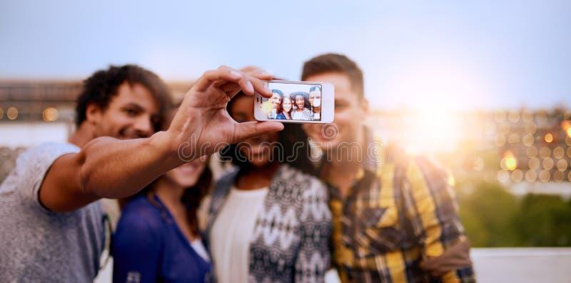 拍与手机的不同种族的millenial小组朋友一张selfie照片在屋顶terrasse在日落 免版税库存图片