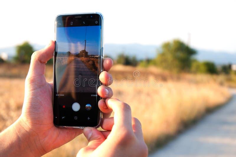 拍与手机的人一张照片 免版税库存照片