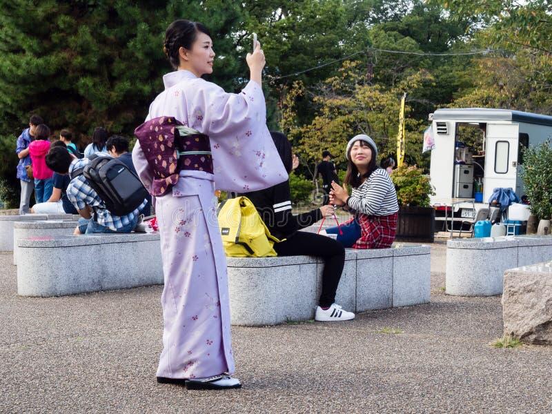 拍与手机的和服的妇女照片 免版税图库摄影