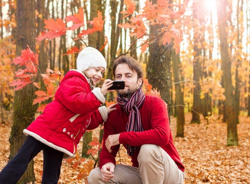 拍与手机的女孩孩子和父亲秋天照片 免版税图库摄影
