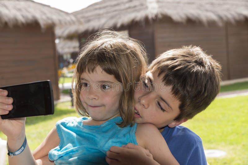 拍与手机的孩子照片 图库摄影