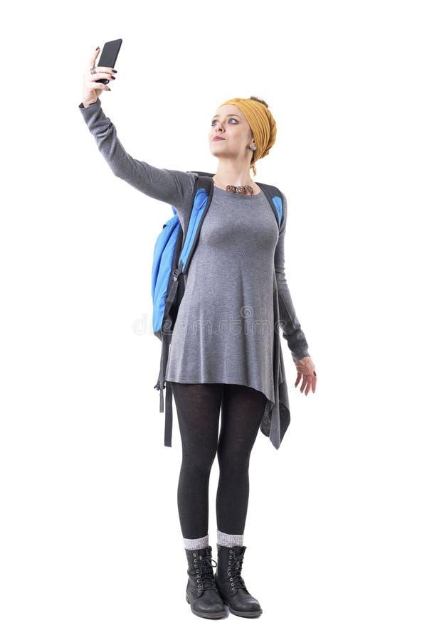 拍与手机的逗人喜爱的轻松的年轻背包徒步旅行者妇女探险家照片 免版税库存照片