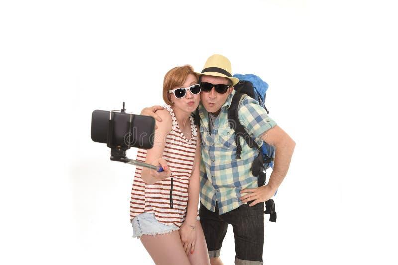 拍与手机的年轻有吸引力和别致的美国夫妇selfie照片隔绝在白色 免版税图库摄影