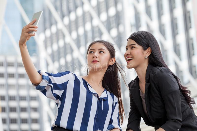 拍与智能手机的两个亚裔女朋友selfie照片在都市 库存图片