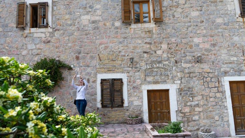 拍与智能手机的女孩照片在有房子和木窗口的石门面的老镇 在地中海的白色毛线衣 免版税库存图片