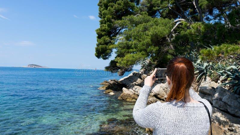 拍与智能手机的年轻红色顶头妇女照片对在假日夏天海岸的蓝色亚得里亚海干净和透明水 库存照片