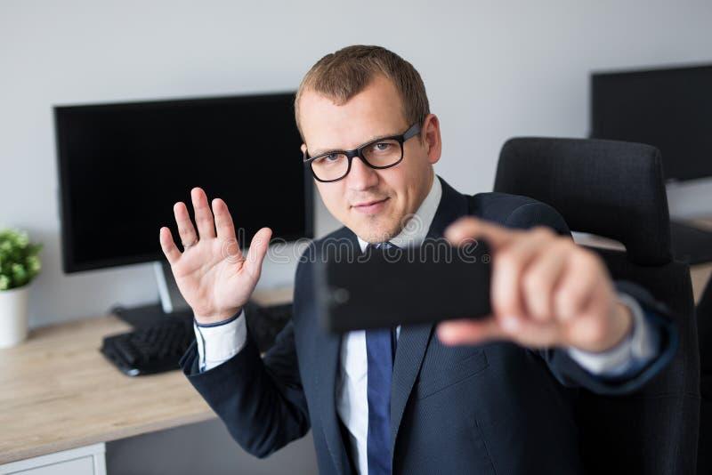 拍与智能手机的英俊的商人画象selfie照片在办公室 库存图片
