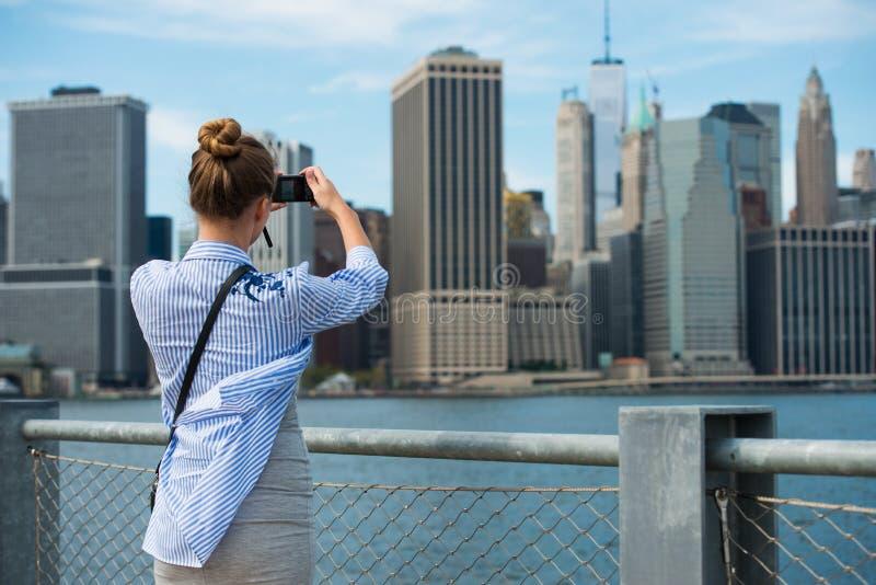 拍与曼哈顿地平线和纽约地平线照相机的旅游妇女旅行照片在秋天假日期间 免版税图库摄影