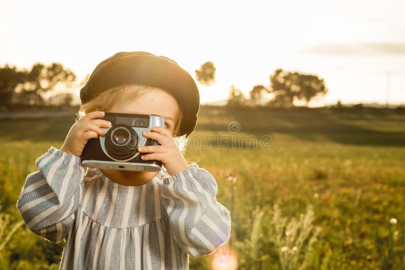 拍与照相机的女孩的画象照片 儿童使用的概念 库存照片