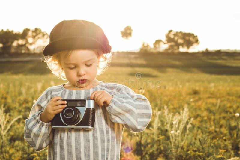 拍与照相机的女孩的画象照片 儿童使用的概念 图库摄影