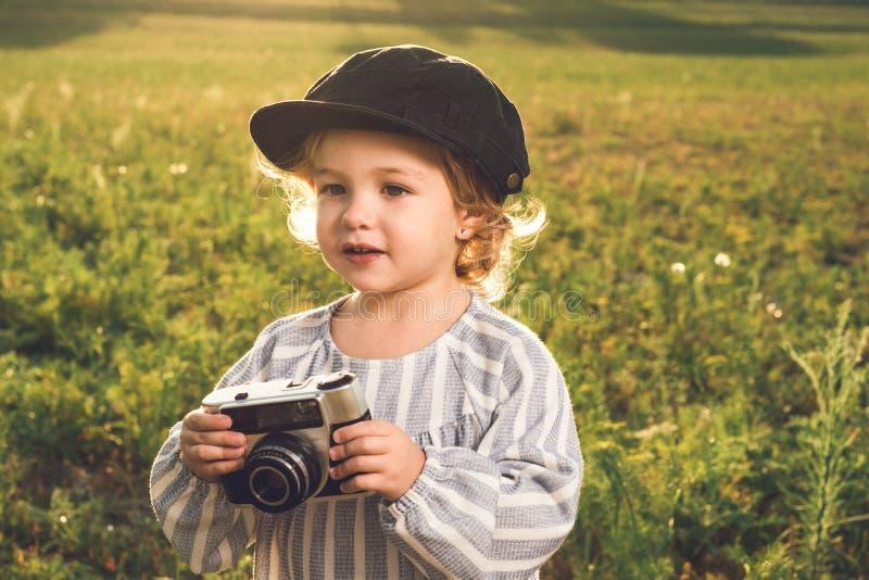 拍与照相机的女孩的画象照片 儿童使用的概念 免版税库存照片