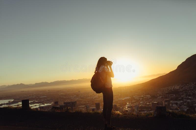 拍与照相机的女性旅客照片 免版税图库摄影