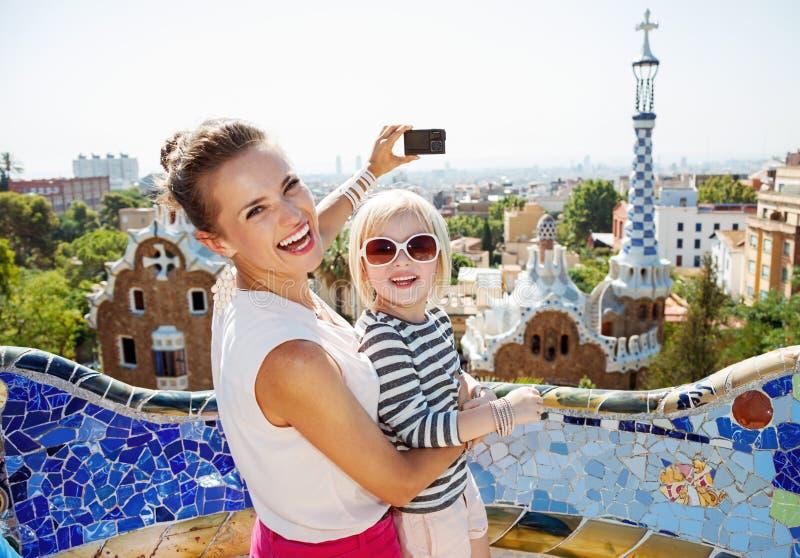 拍与照相机的微笑的母亲和婴孩照片在公园Guell 库存照片