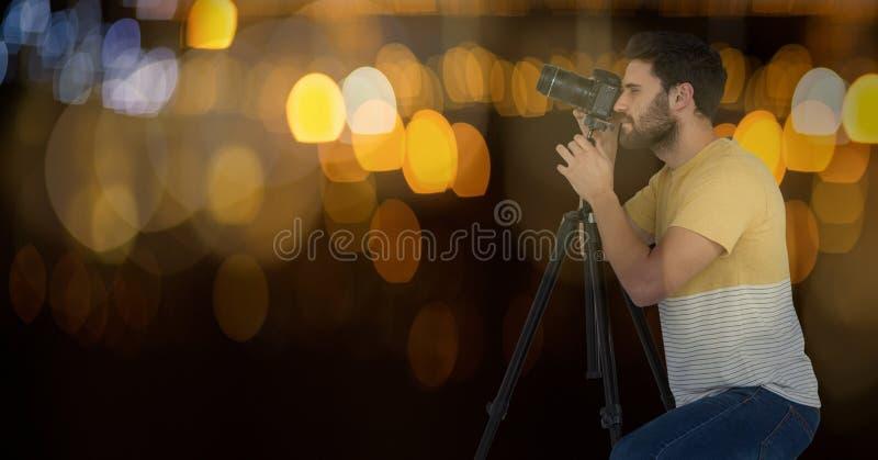 拍与照相机的摄影师一张照片在三脚架 蓝色和黄色bokeh背景和boke 免版税库存照片