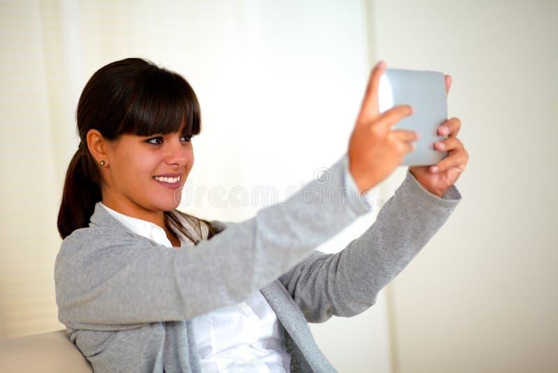 拍与片剂个人计算机的微笑的少妇照片 图库摄影