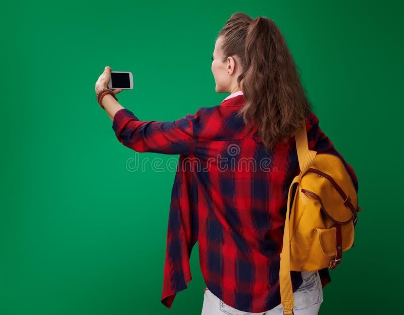 拍与电话的学生妇女照片在绿色背景 库存图片