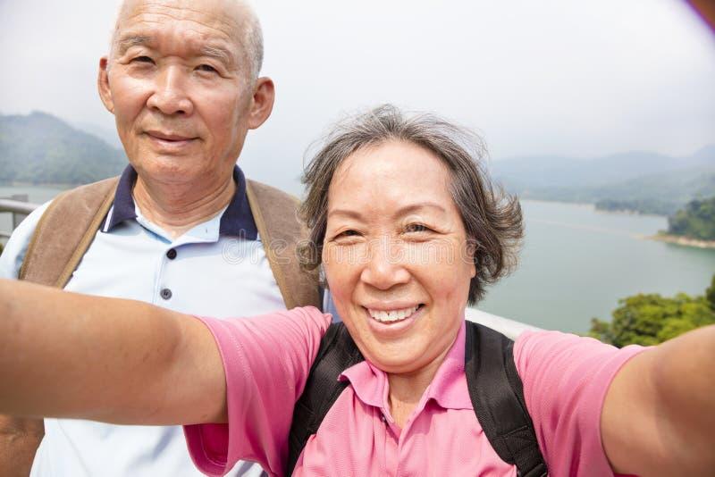 拍与聪明的电话selfie的愉快的资深夫妇照片 免版税库存图片