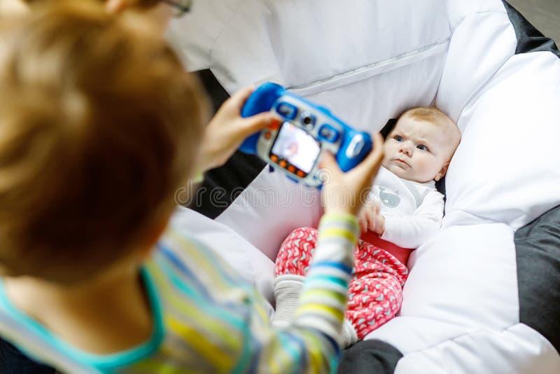 拍与逗人喜爱的女婴玩具照相机的两个兄弟姐妹孩子男孩照片  免版税库存图片