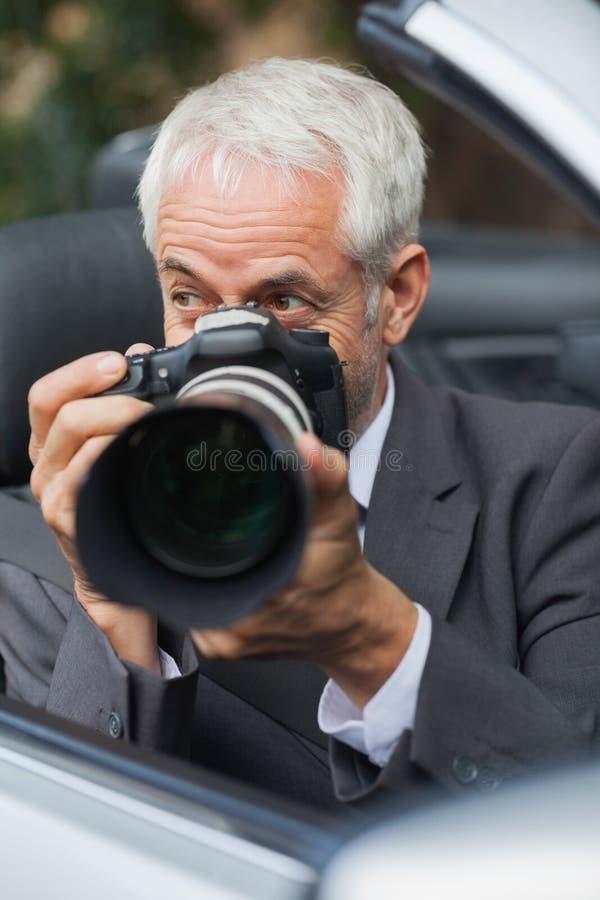 拍与他的专业照相机的成熟无固定职业的摄影师照片 免版税库存图片
