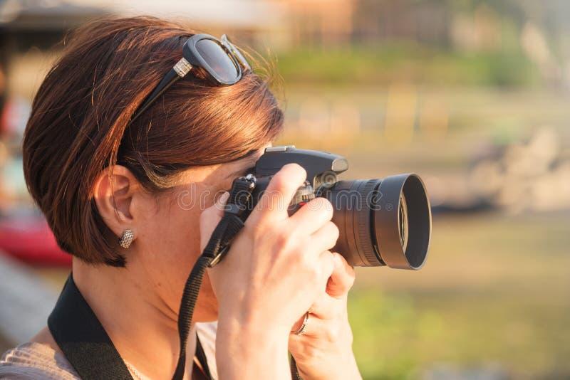 拍与DSRL照相机的妇女摄影师照片 免版税图库摄影