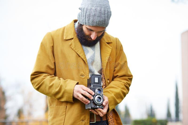 拍与TLR照相机的年轻有胡子的行家照片 库存图片