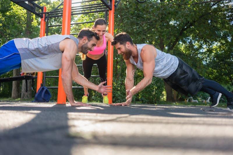 拍从板条位置的两个年轻人手在伙伴锻炼期间在公园 免版税库存照片