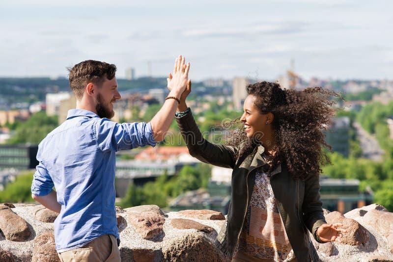 拍他们的手立陶宛的年轻微笑的多种族夫妇 免版税图库摄影