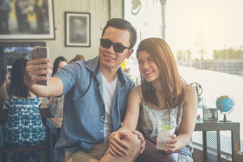 拍他们的照片的夫妇由手机 免版税库存照片