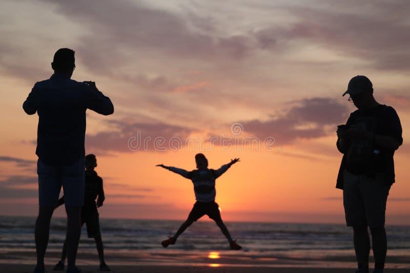 拍他的儿子的照片人跳跃入日落由在法国silouette的海洋海边 免版税库存照片
