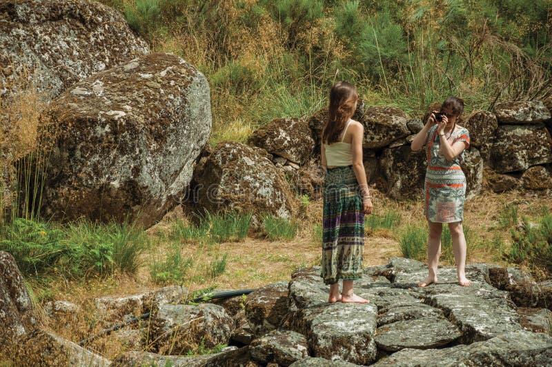 拍另一个女孩的照片在岩石风景中的女孩 免版税库存图片