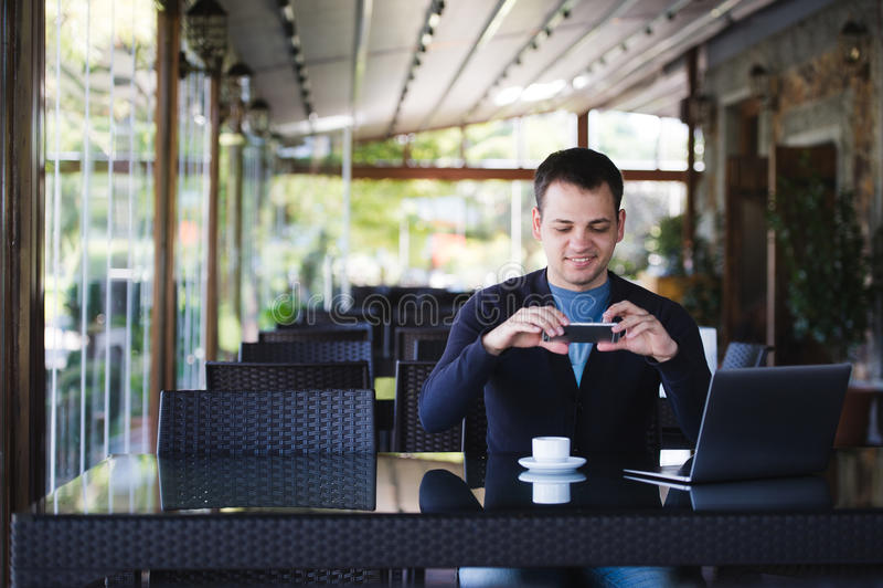 拍咖啡杯的照片和使用膝上型计算机的年轻学生人在军用餐具在大学或街道咖啡馆 免版税库存照片