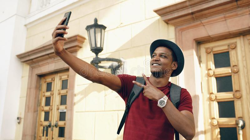 拍在他的智能手机照相机的混合的族种愉快的旅游人selfie照片站立在著名大厦附近在欧洲 库存照片