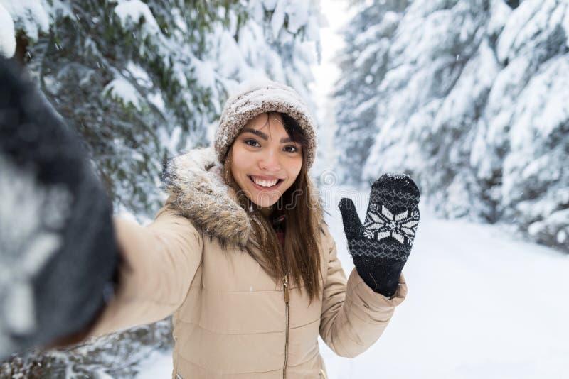 拍在冬天雪森林女孩的年轻亚洲美丽的妇女微笑照相机Selfie照片户外 库存照片