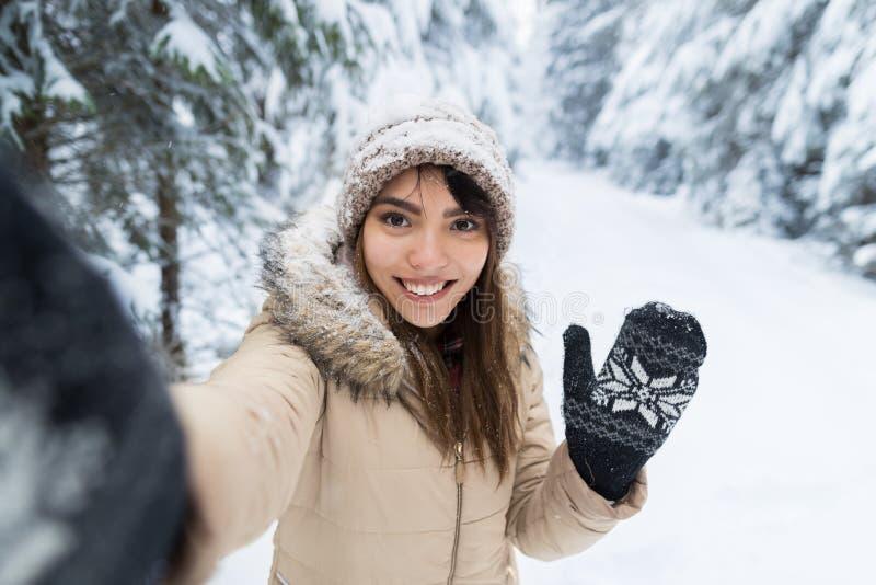 拍在冬天雪森林女孩的年轻亚洲美丽的妇女微笑照相机Selfie照片户外 免版税库存图片