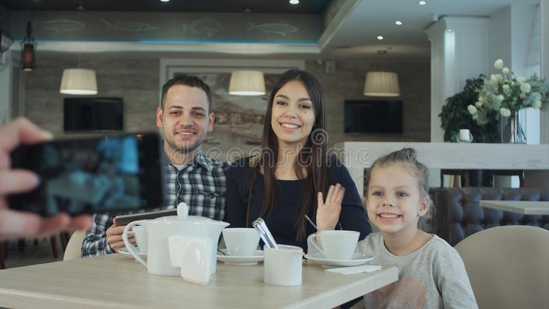 拍在年轻愉快的家庭手机的某人照片在咖啡馆的 库存图片