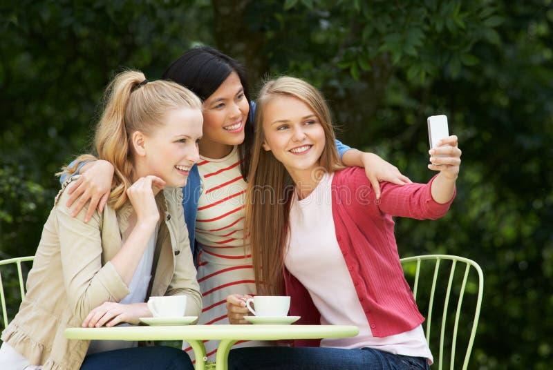 拍在手机的十几岁的女孩照片在室外咖啡馆 免版税库存图片
