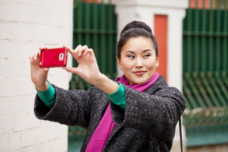 拍在手机的年轻美丽的妇女游人照片 库存图片