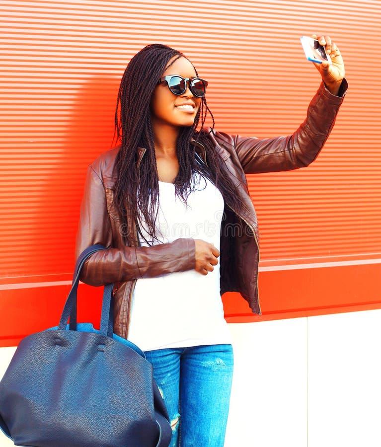 拍在智能手机的时髦的非洲妇女自画象照片 免版税库存图片
