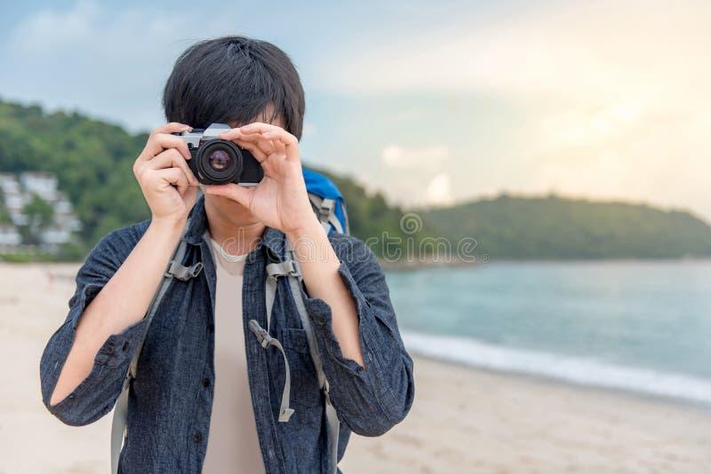 拍在海滩的年轻亚裔人摄影师照片 免版税库存照片