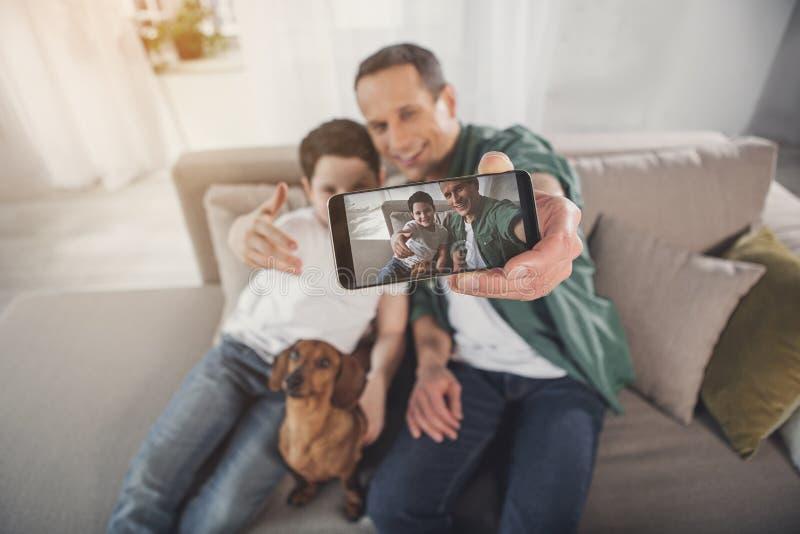 拍在电话照相机的快乐的家庭照片 免版税图库摄影