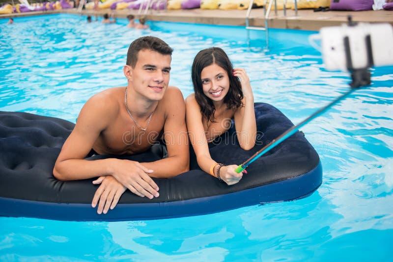 拍在电话的夫妇特写镜头selfie照片用selfie棍子在水池的床垫和他们的夏天周末 免版税库存图片