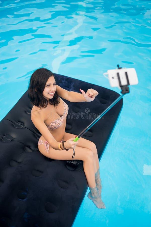 拍在电话的selfie照片用selfie棍子和显示好类的赞许姿态在床垫的女孩在水池 免版税库存照片