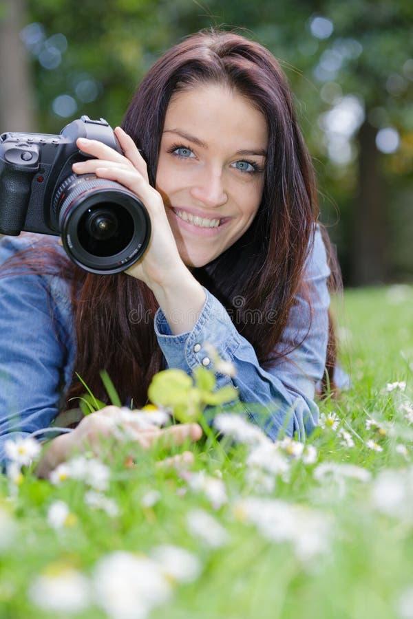 拍在草的年轻女性摄影师照片 库存照片