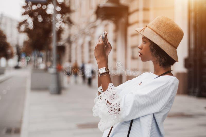 拍在街道上的非裔美国人的女孩照片通过手机 库存图片