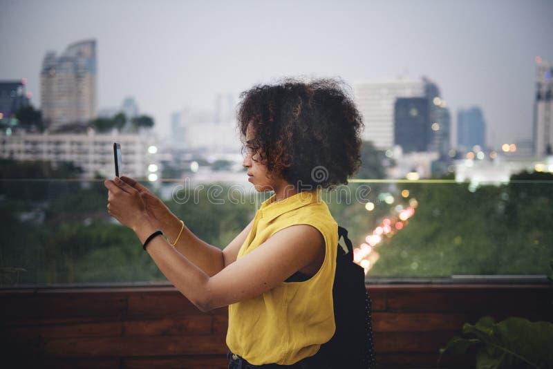 拍在都市风景的少妇一张照片 免版税库存图片