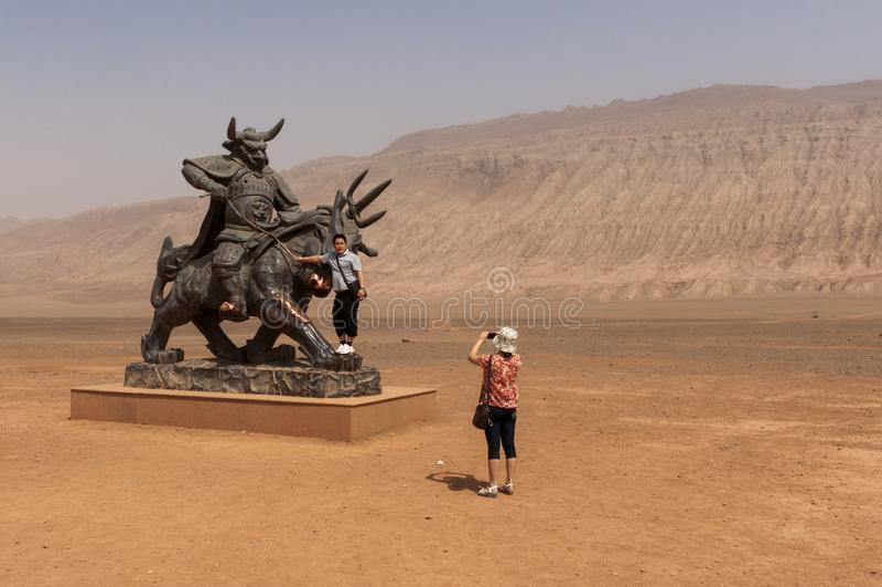 拍在雕象在火焰状山附近,新疆前面的中国游客照片 库存图片