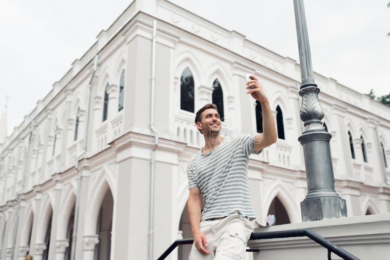 拍在他的手机的年轻英俊的人一张照片,当游览外国城市时 免版税库存照片