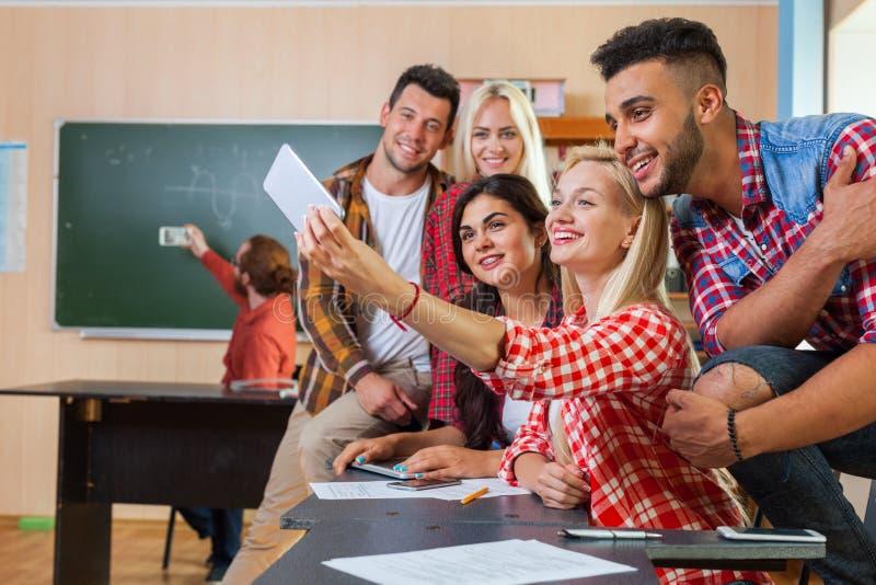 拍在细胞巧妙的电话,混合种族人愉快微笑的年轻学生团体Selfie照片 免版税库存图片