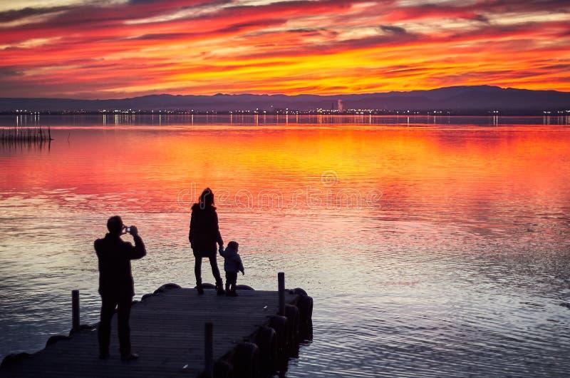 拍在Albufera de巴伦西亚,西班牙的镇静水的日落的家庭照片 免版税库存照片