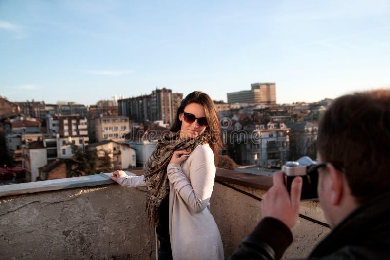 拍他俏丽的女朋友的照片年轻人 享用在屋顶的太阳和人的浪漫夫妇拍图片